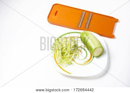 Grater and grated zucchini. Selective focus. Macro