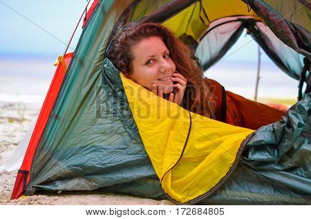 beautiful girl lies in a tent on the beach in summer