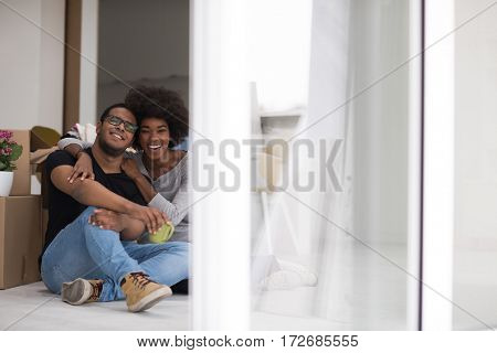 Relaxing in new house. Cheerful young African American couple sitting on the floor and drinking coffee while cardboard boxes laying all around them
