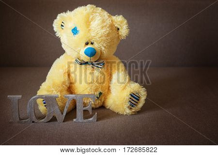 A word LOVE made of wood and a yellow teddy bear in blue bow tie on textile background.