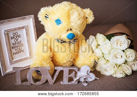 A word LOVE made of wood, a wooden decorative heart, white roses flowers and a yellow teddy bear in blue bow tie background. Do more of what makes you happy,