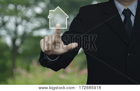 Businessman pressing house icon over blur flower and tree in parkd Real estate concept