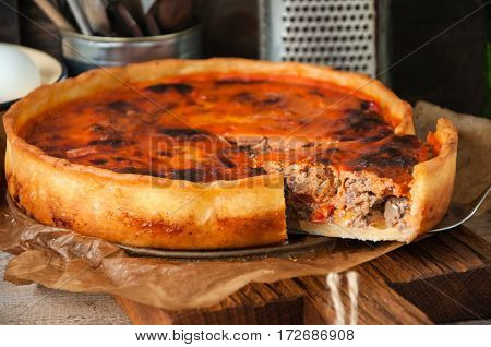 Vegetable and meat open pie on a board. Rustic style. Toned.