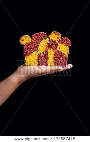 Carrot and beetroot bread with poppy seeds in a girl's hand