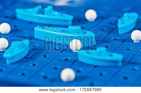 Toy War Ships And Submarine Are Placed On The Blue  Playing Board