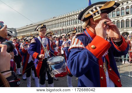 Venice, Italy - February 19 2017: Carnival band parade at St Marks Square. A band dressed in traditional costumes plays music and marches at Piazza San Marco during Venice Carnival 2017.