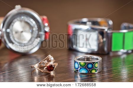 Multi-colored Silver Ring And A Gold Ring With A Ruby On A Background Of Watches