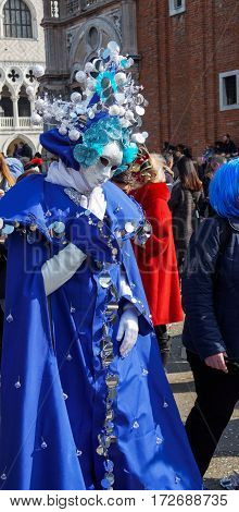 Venice, Italy - February 19 2017: Carnival mask and costume poses. Masked person in traditional costume poses at PIazza San Marco for the Venice 2017 Carnival.