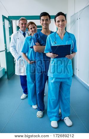 Portrait of smiling surgeons and doctors standing in corridor at hospital