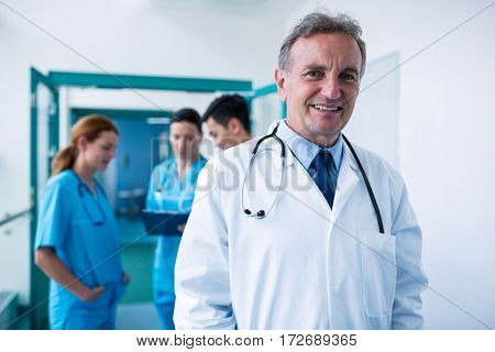 Portrait of smiling doctor standing in corridor at hospital