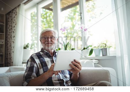 Portrait of senior man using digital tablet at home