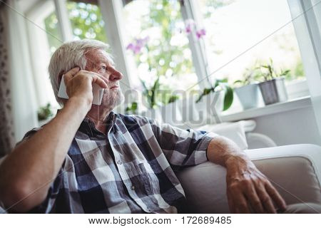 Senior man talking on mobile phone at home