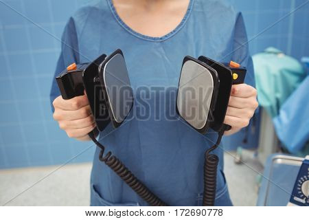 Mid section of female surgeon holding defibrillator at the hospital