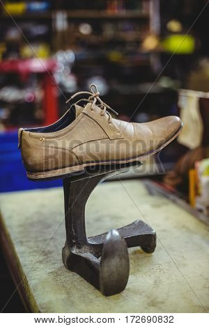 Leather shoe on shoe repair stand in workshop