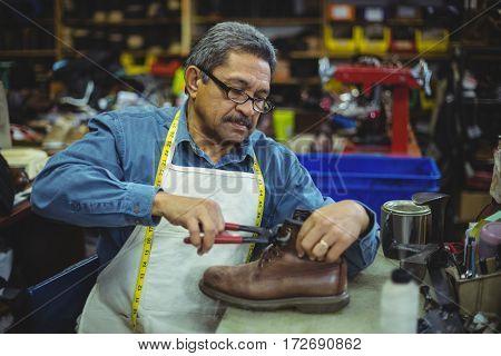 Shoemaker repairing a shoe in workshop
