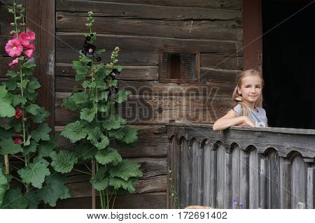 beautiful girl posing at porch wooden house