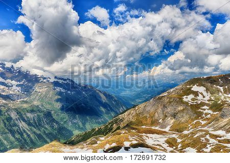 capped mountain peaks and blue sky with clouds