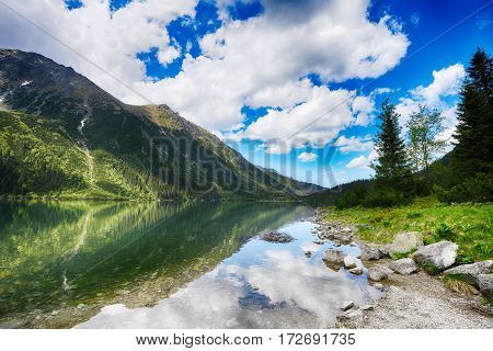 clear lake among mountain ranges under blue sky