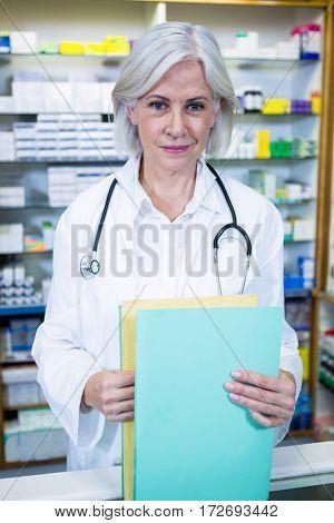 Portrait of pharmacist holding files in pharmacy