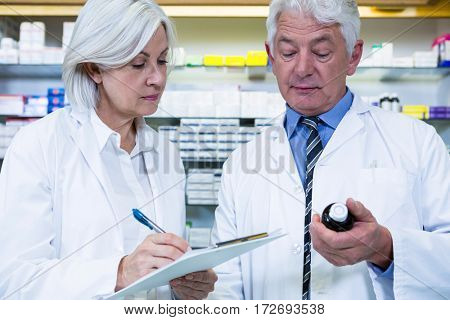 Pharmacists checking and writing prescription for medicine in pharmacy