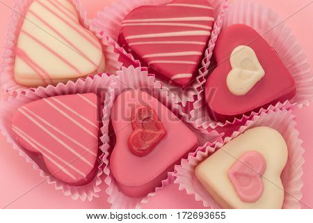 Pink heart shaped petit fours cakes seen from above on a pink background