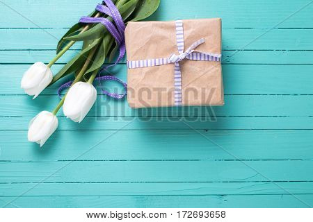 Bunch of white tulips flowers with violet ribbon and present in box on turquoise background. Place for text. Selective focus.