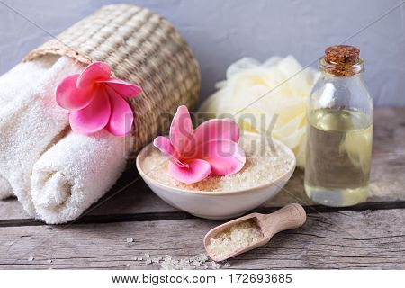 Spa or wellness setting. Sea salt in bowl towels bottles with aroma oil and flowers on vintage wooden background. Selective focus.
