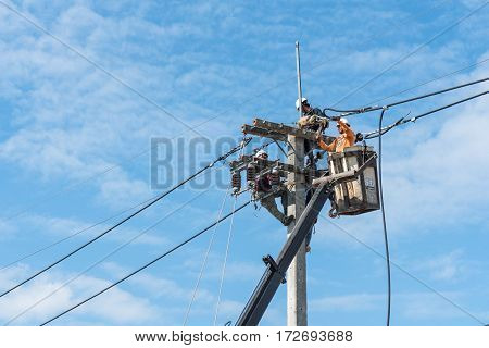 KALASIN THAILAND - DECEMBER 23 2016: Electricians at height in bucket of hydraulic lift platform truck installing new high voltage power lines.