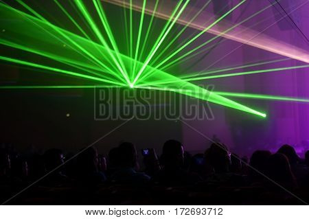 Unrecognizable people watching a beautiful laser show with multicolored lights