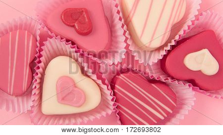 Pink heart shaped petit fours cakes seen from above in a banner size frame on a pink background