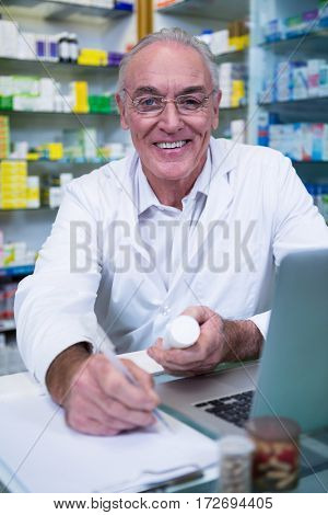 Portrait of pharmacist writing prescriptions for medicines in pharmacy