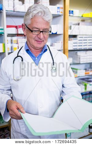Pharmacist reading prescriptions in pharmacy