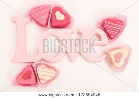 Pink heart shaped petit fours cakes seen from above decorated around pink letters stating Love on a white background