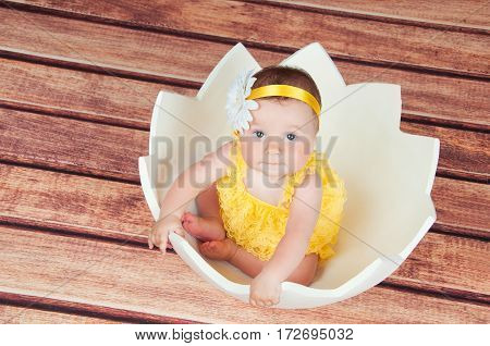 Cute little girl in the egg basket. View from above.