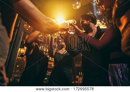 Low angle shot of group of friends enjoying drinks at bar together. Young people at nightclub toasting cocktails.