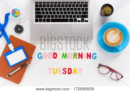 Caption word Good morning tuesday. White office desk with laptop diary eyeglasses compass pen blank identification card and cup of coffee on white background.
