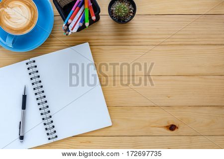 Office desk table with leather notebookpencolor pencil and cup of coffee.Top view with copy space.Working desk table concept.