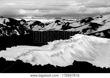 Unreal view from the volcano Ok with its snow-filled crater to the snowfields and glaciers of Thorisdalur. The large Langjokull glacier is in the background.