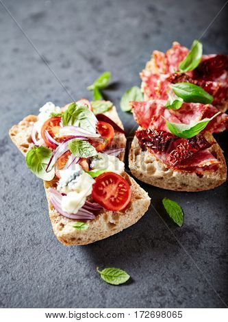 Mediterranean-style ciabatta sandwiches with salami, dried tomatoes, gorgonzola and cherry tomatoes