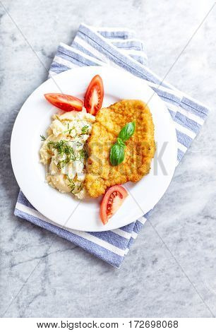 Schnitzel with mashed potatoes and tomatoes