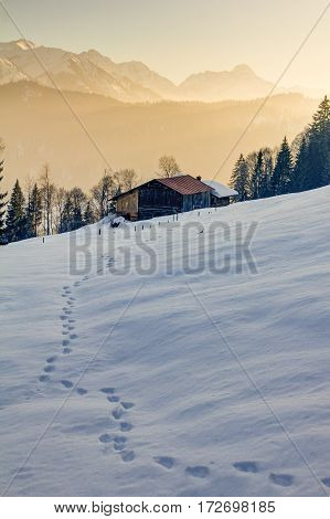 Footprints in snow towards a wooden cabin with a great view to the orange illuminated Allgauer Alps