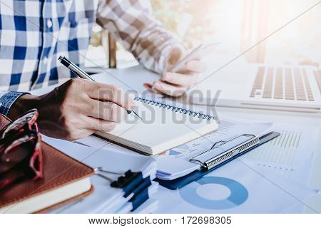 Businessman hands with pen writing notebook and using smart phone on office desk table close up. Business concept.