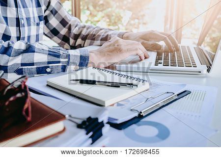 Businessman working laptop for new architectural project. Generic design notebook on the table.Business analysis and strategy concept.