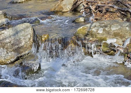 A close up of the icicles and stream on small river.