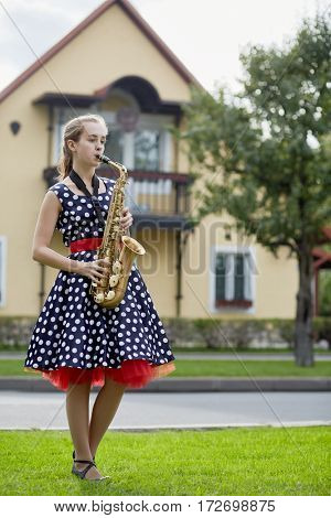 Teenage girl plays saxophone on grassy lawn near road against two-storied house.