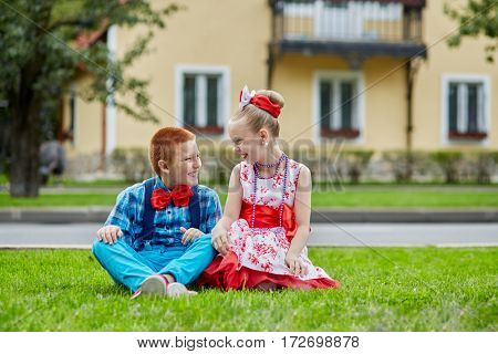 Smiling boy and girl in dancing suits sit on grassy lawn and look at each other against two-storied house.