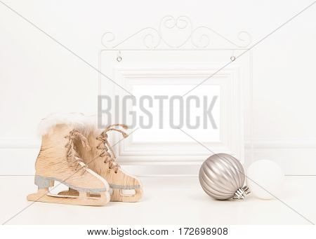 Empty white picture frame with space for text or wishes in a white living room setting with white and wooden christmas and winter decoration