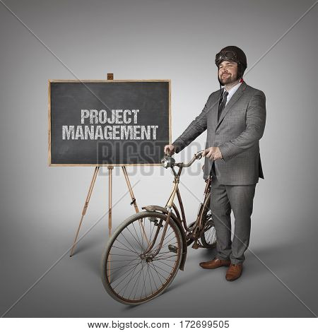 Project Management text on blackboard with businessman and vintage bike