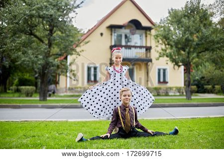 Smiling boy sits on side split and girl in polka-dotted dress stands behind him on grassy lawn against two-storied house.