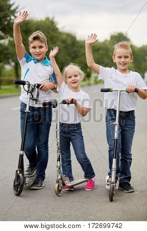 Two boys and girl in t-shirts on scooters stand on road and wave hands.
